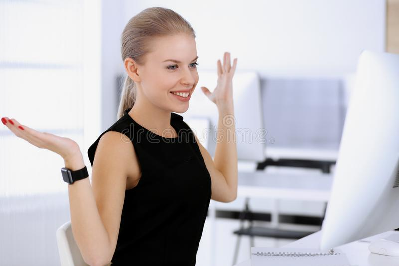 Business woman happy and excited while working with computer in modern office. Secretary or female lawyer looks royalty free stock photography