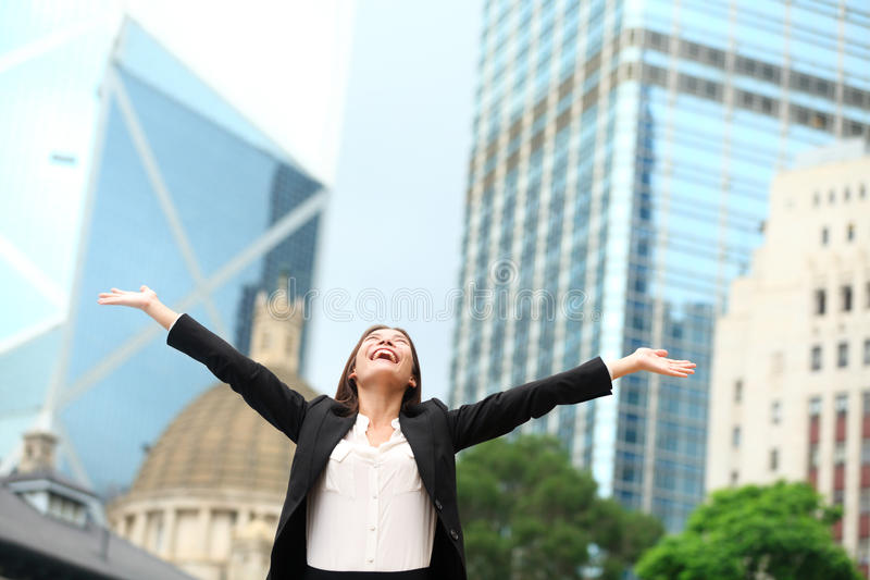 Business woman happy success outdoor in Hong Kong. Celebrating successful business with arms spread out winning. Young multiracial Chinese Asian / Caucasian stock image