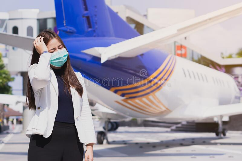 The business woman has a headache from coronavirus and pm 2.5 in front of airplane. Coronavirus and Air pollution pm 2.5 concept. The business woman has a royalty free stock image