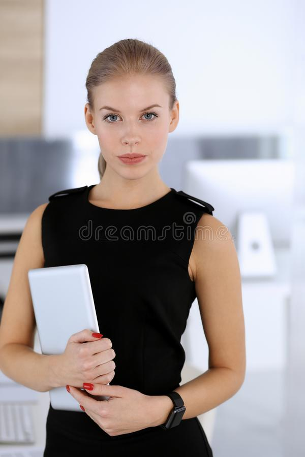 Business woman headshot while lady using tablet computer in modern office. Secretary or female lawyer looks beautiful in stock images