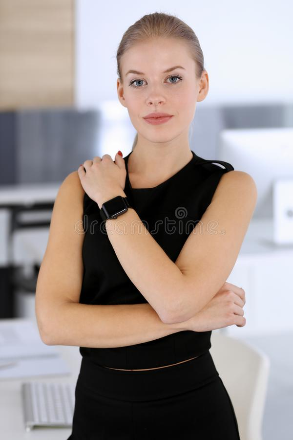 Business woman headshot in modern office. Secretary or female lawyer looks beautiful in black dress. Business people royalty free stock photos