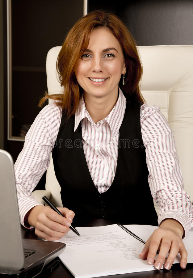 Business Woman at her desk. Beautiful business woman at her desk royalty free stock photos