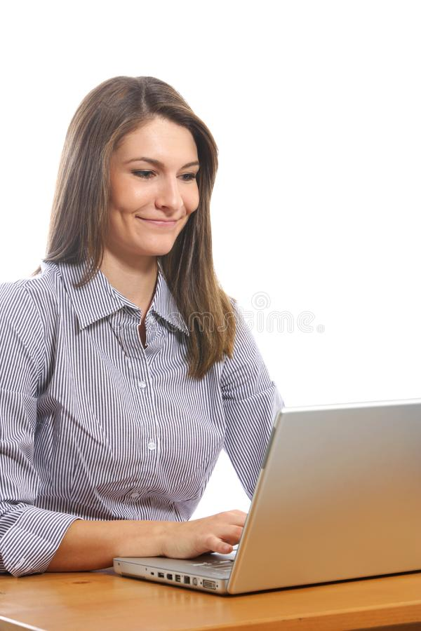 A business woman on her laptop at a desk stock photo