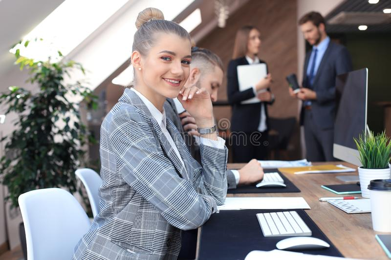 Business woman with her staff, people group in background at modern bright office indoors. stock image