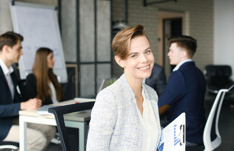 Business woman with her staff, people group in background at modern bright office indoors. royalty free stock images