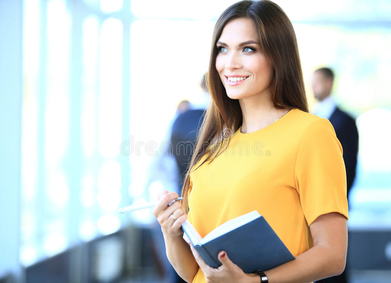 Business woman with her staff, people group in background. Business women with her staff, people group in background at modern bright office indoors stock image