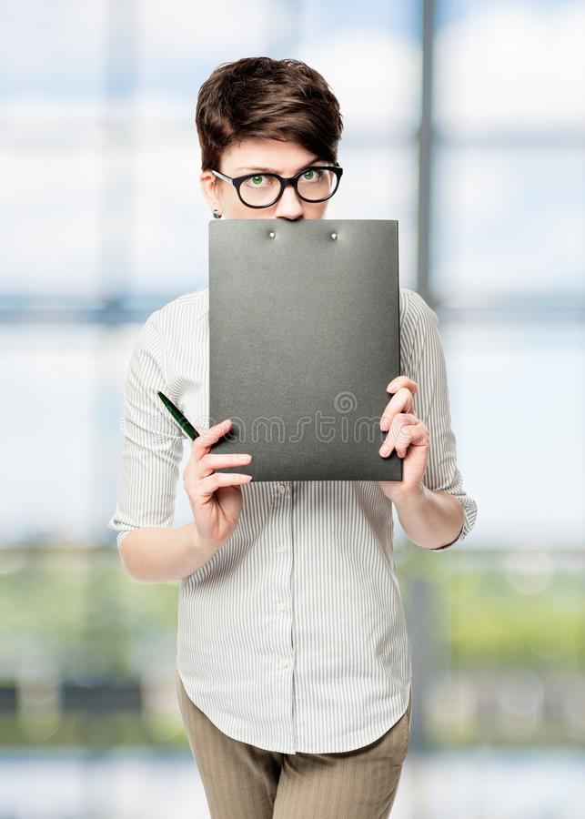 Business woman hiding behind a black folder stock images
