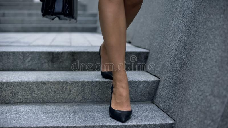 Business woman in high heels walking down stairs, tired legs, varicose veins royalty free stock image