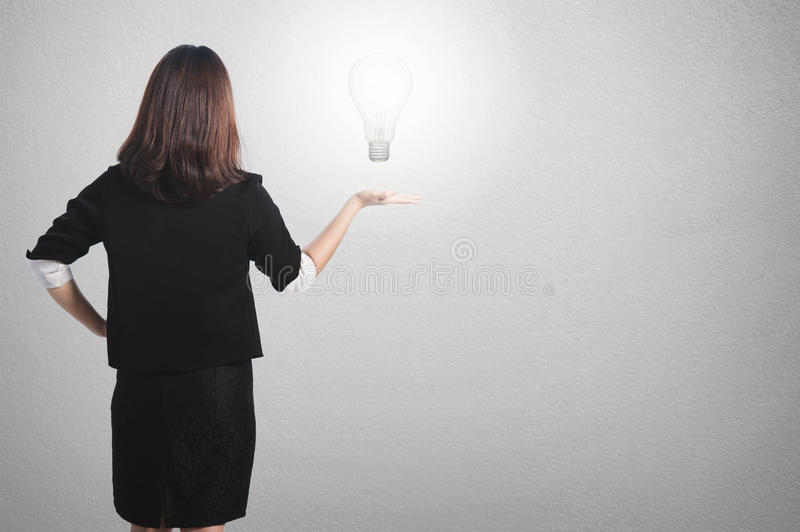 Business woman holding idea bulb wall for her plan. Asia Business woman holding idea bulb wall background stock photography