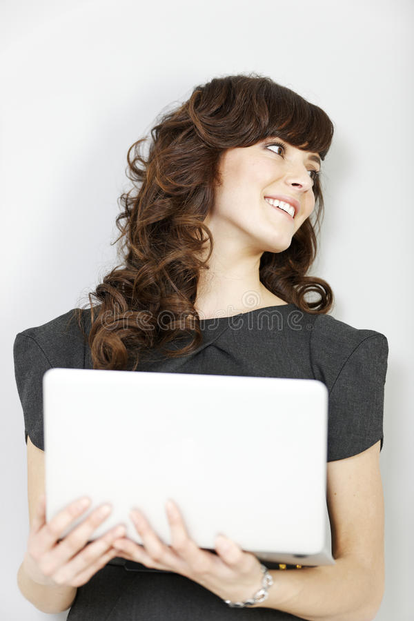 Business woman holding laptop. Professional young business woman holding a laptop computer stock photo