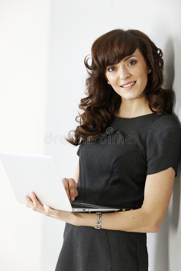 Business woman holding laptop. Professional young business woman holding a laptop computer royalty free stock images