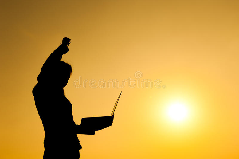 Business woman holding laptop at sunset silhouette. Happy Business woman holding laptop at sunset silhouette stock photography