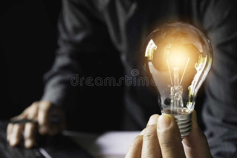 Business woman holding light bulb on the desk in office and using computer in financial,accounting,energy,idea concept.  stock photography