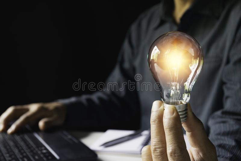 Business woman holding light bulb on the desk in office and using computer in financial,accounting,energy,idea concept.  royalty free stock photo