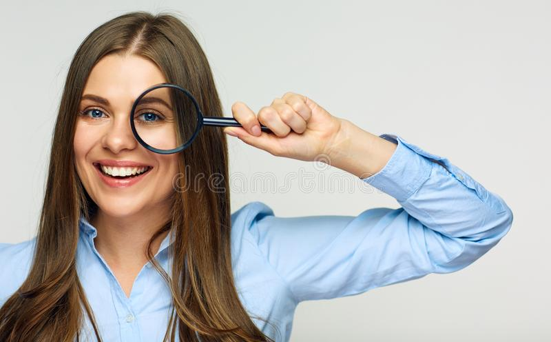 Business woman holding magnifying glass behind eyes. Smiling business woman portrait stock photography