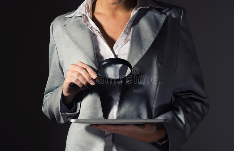 Business woman holding a magnifying glass. Business woman looking for a problem in the plate, the concept of information security royalty free stock photo