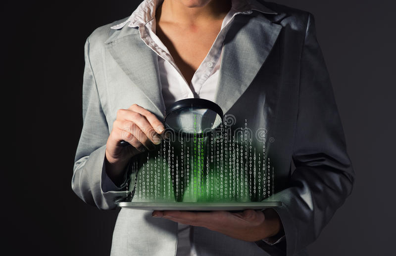 Business woman holding a magnifying glass. Business woman looks at the binary code of the tablet computer, the concept of information security stock photo