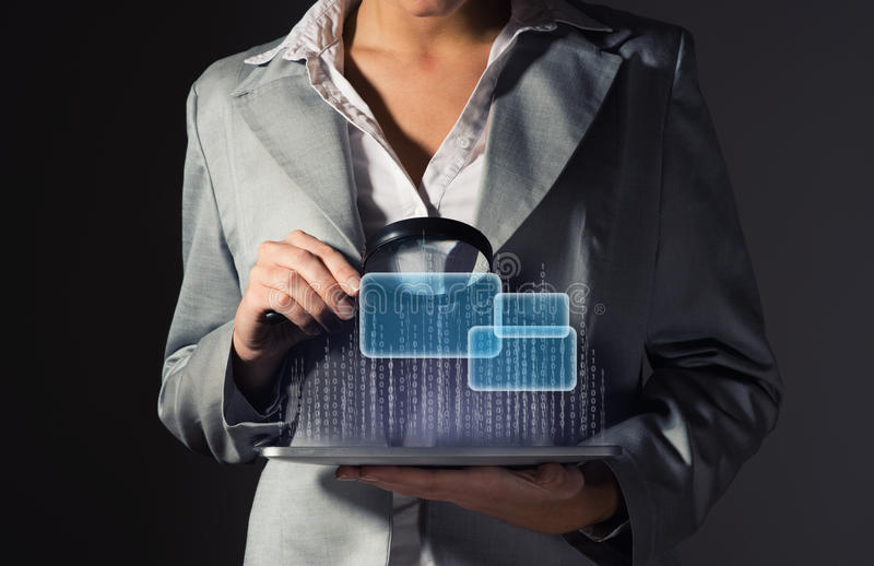 Business woman holding a magnifying glass. Business woman looks at the binary code of the tablet computer, the concept of information security royalty free stock photography