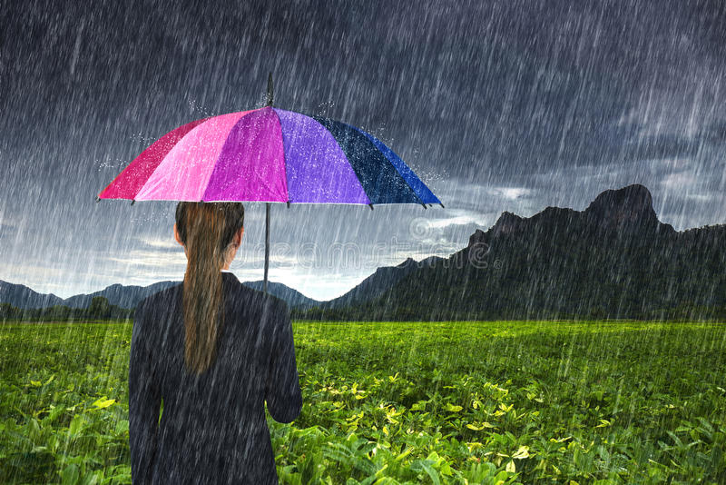 Business woman holding multicolored umbrella with falling rain at Khao Jeen Lae. Lopburi, Thailand royalty free stock photography