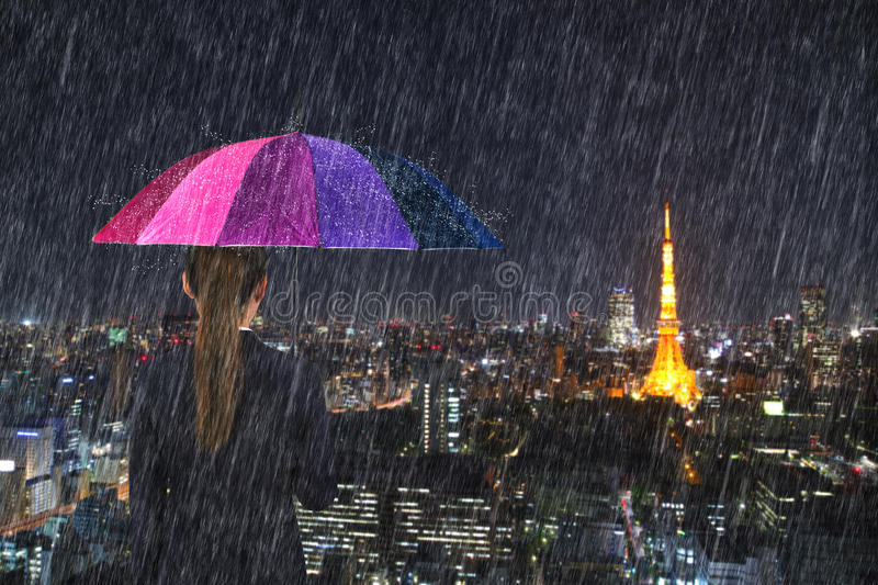 Business woman holding multicolored umbrella with falling rain a royalty free stock photos