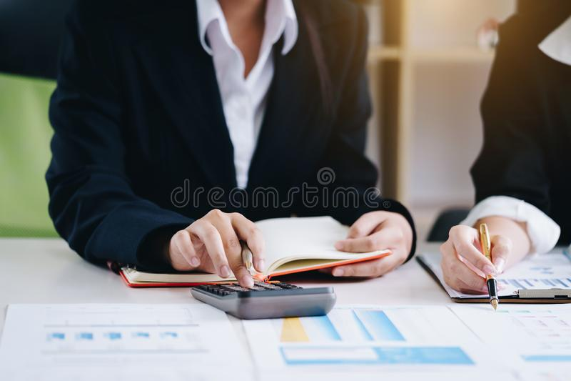 Business woman holding a pen pointing the report and partnership to analyze the marketing plan with calculator on wooden table in royalty free stock image