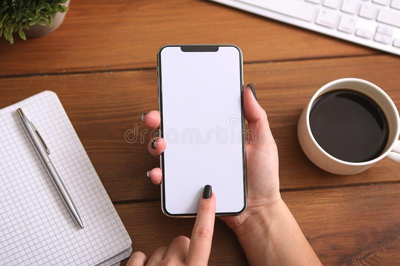 Business woman holding phone with white empty screen at work place. top view stock photos