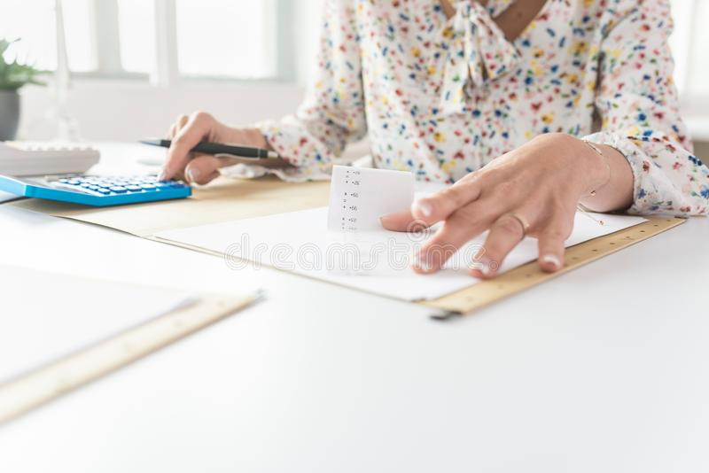 Business woman holding a printout receipt while she uses it to m royalty free stock image