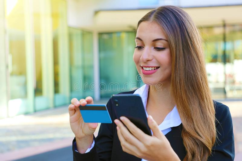 Business woman holding smart phone reading credit card number making shopping online outdoor office on break time. People and stock photo