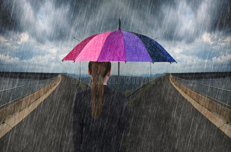 Business woman holding umbrella with falling rain on cross road. Business woman holding multicolored umbrella with falling rain on cross road spliting in two way royalty free stock photo