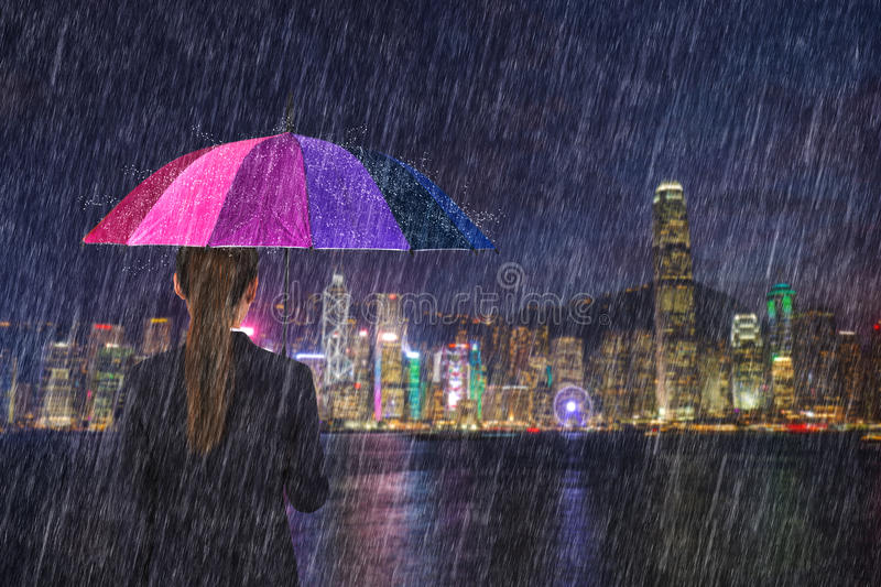 Business woman holding umbrella with falling rain at victoria ha. Business woman holding multicolored umbrella with falling rain at victoria harbour, Hong Kong royalty free stock images