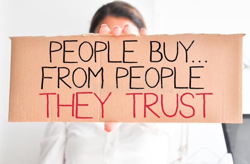 """Business woman holding white card with text """"people buy from people they trust"""" stock photography"""