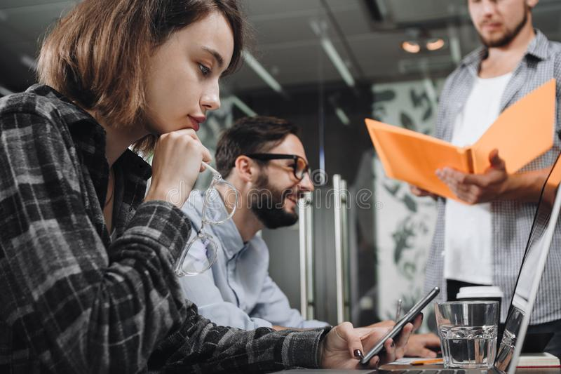 Business woman holds glasses in his hand and thinks on new stratup together with his team. Coworking team discussing new startup royalty free stock photos