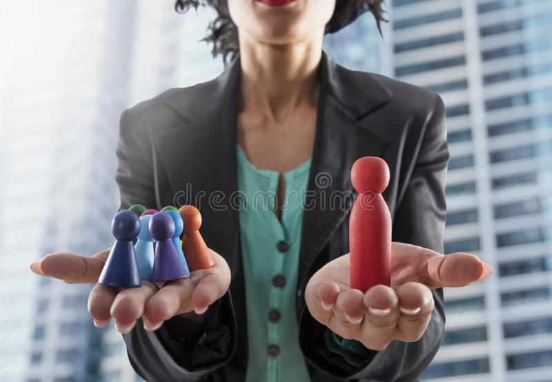 Business woman holds wooden toy shaped as person. Concept of business teamwork and leadership stock photos