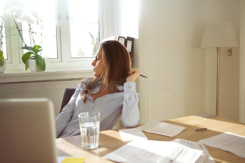 Business woman in home office looking away thinking. Beautiful caucasian female sitting at table with glass of water, documents and laptop. Business woman in royalty free stock images