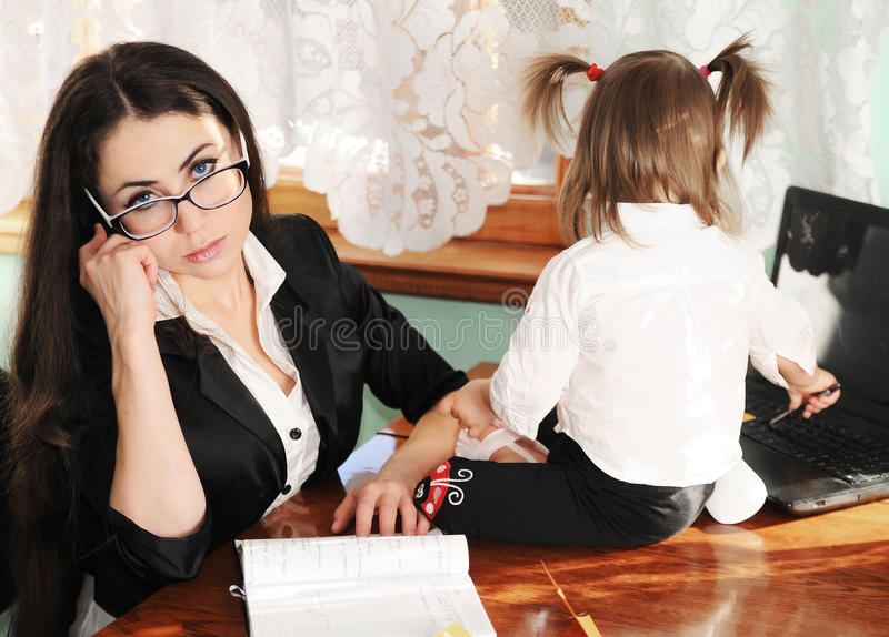 Business woman at home. Business woman tries to work at home,taking care of her child royalty free stock image