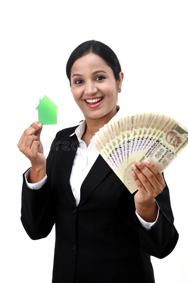 Business woman with house model and Indian currency. Young business woman with house model and Indian rupee notes in hands royalty free stock photos