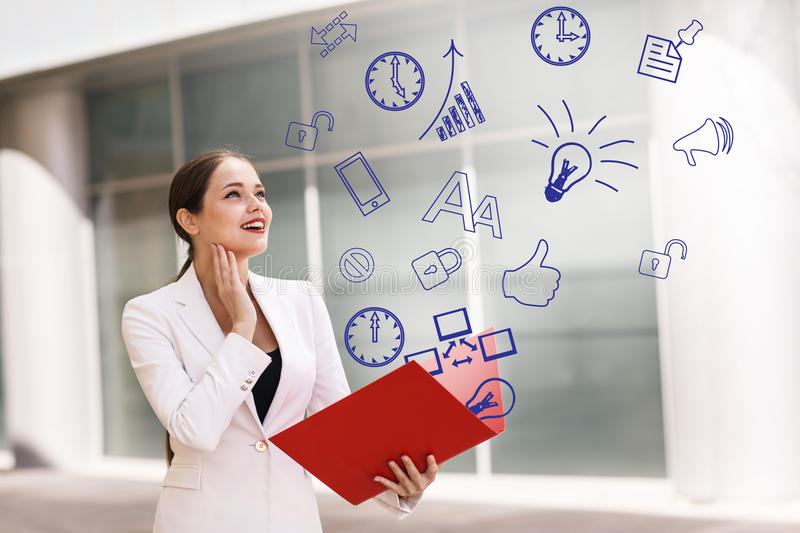Business woman with icons overhead. Happy young business woman with a folder and icons overhead royalty free stock image