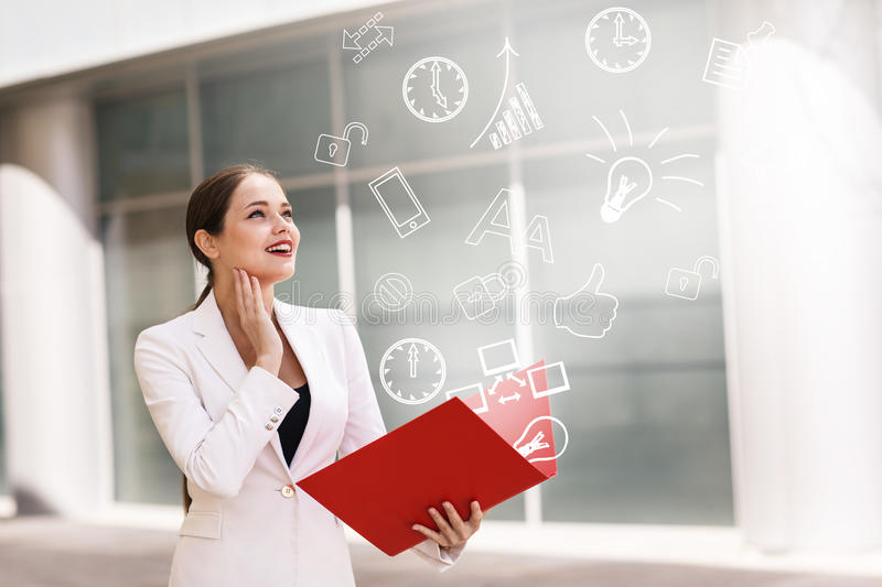 Business woman with icons overhead. Happy young business woman with a folder and icons overhead stock photo