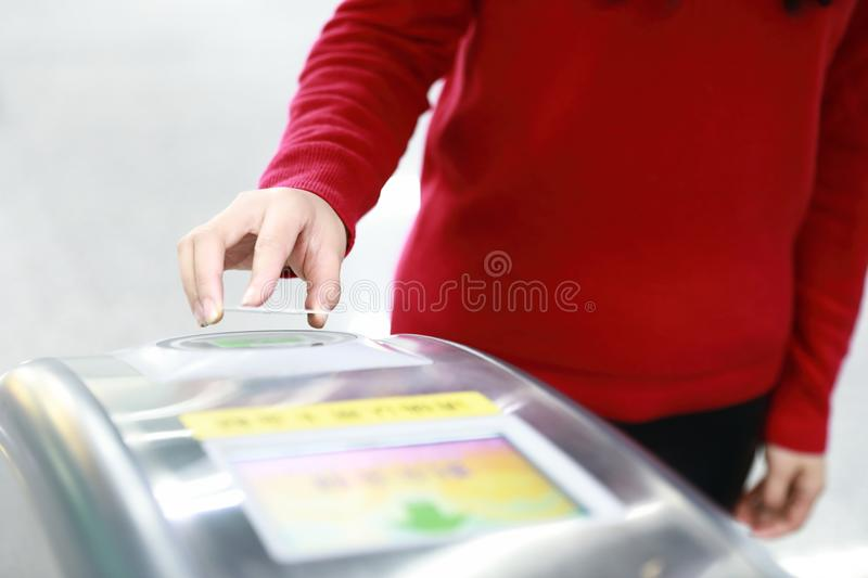 Woman hand traffic card insert ticket to ticket entrance train station royalty free stock images