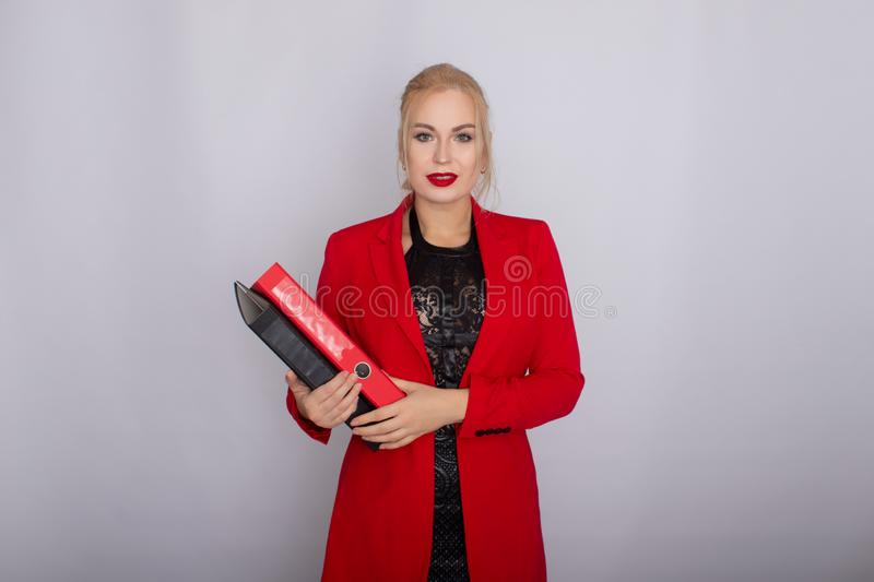Business woman in jacket holding folders in her hands royalty free stock image