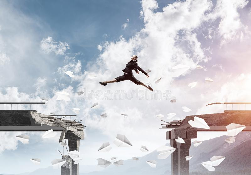 Problems and difficulties overcoming concept. Business woman jumping over gap in bridge among flying paper planes as symbol of overcoming challenges. Skyscape stock photography