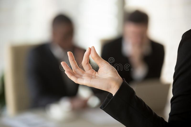 Business woman keeping calm on work concept. Close up image of female palm with fingers folded in Jnana mudra gesture with blurred silhouettes of talking stock image