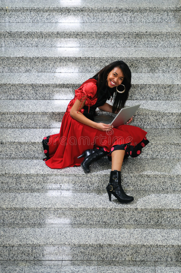 Business woman with laptop on staircase royalty free stock photography