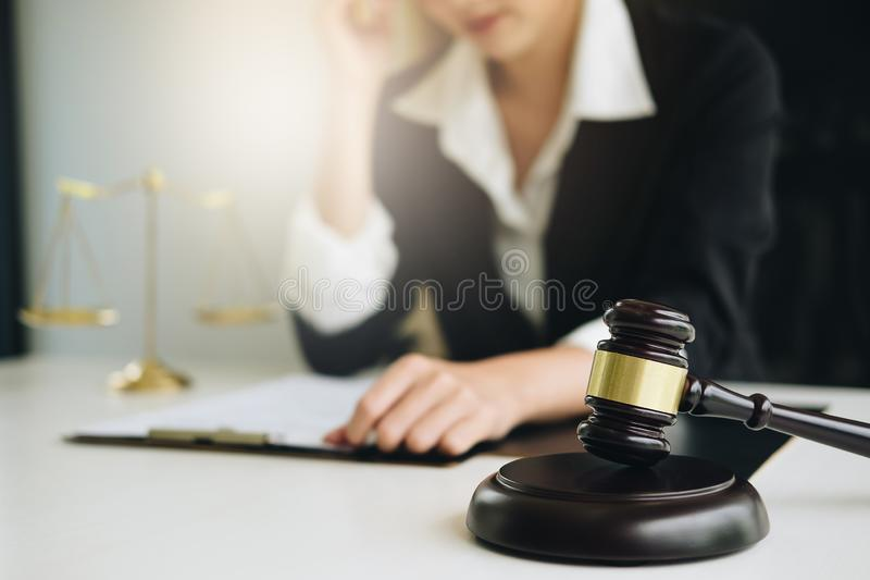 Business woman or lawyers discussing contract papers with brass scale on wooden desk in office. Law, legal services, advice, stock images
