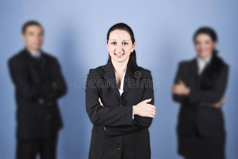 Business woman leader. Young business woman leader standing with hands crossed and smiling for you in the middle of two colleagues partners,check also stock photos