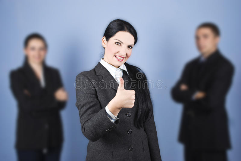 Business woman leader giving thumbs up. In the middle of her colleagues and smiling,concept of successful teamwork,check also royalty free stock photography