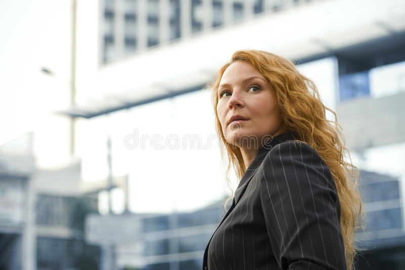 Business woman leader outside the office building. Red-haired business woman leader outside the office building royalty free stock photography