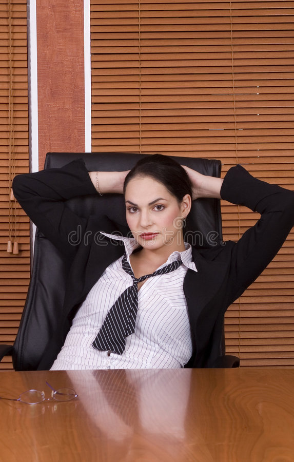 Business woman lean. Brunette business woman with black suit leaning back in chair stock photo