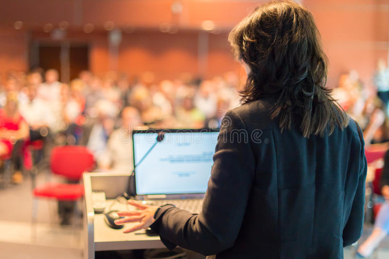 Business woman lecturing at Conference. Audience at the lecture hall stock image