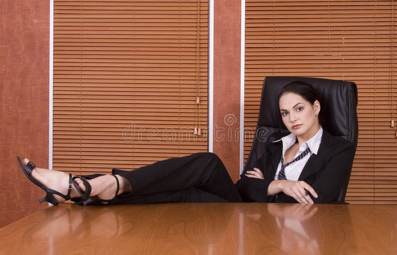 Business woman legs on desk. Brunette business woman with black suit with legs on desk royalty free stock photo